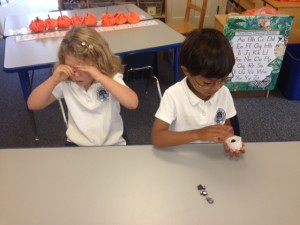 A student covers her eyes, while her partner hides some erasers. How many are under the cup?